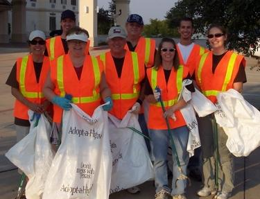 Cleanup group in orange vests and holding trash bags